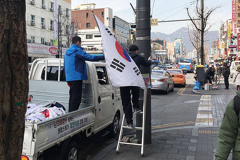 仕方なく車から降りて、脚立を取り出し柱に立てかけ登って国旗
