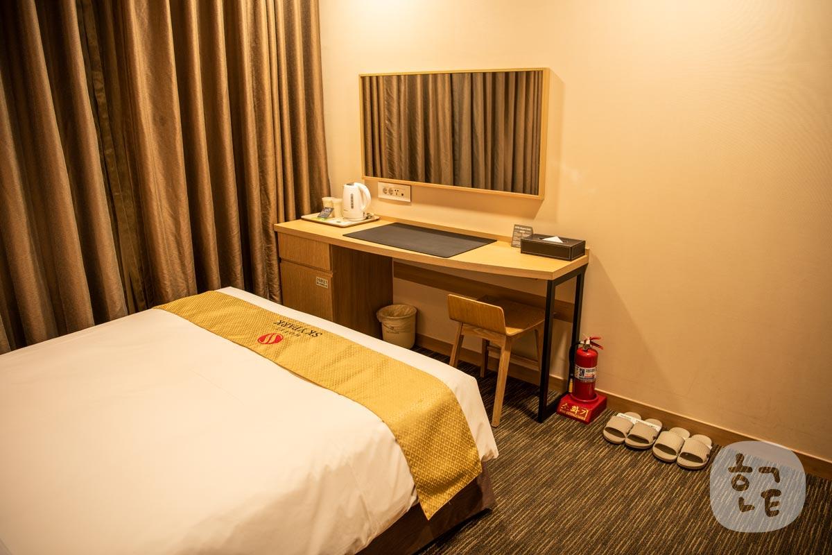 ベッドの前には大きな鏡・化粧台があり、仕事もできるスペース
